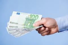 提供援助欧洲钞票的商人的手 库存图片