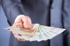 提供援助欧洲钞票的商人的手 免版税库存照片