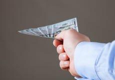 提供援助美元的商人的手 免版税库存照片