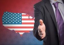 提供他的有美国国旗的一部分的一个人手在背景中 图库摄影