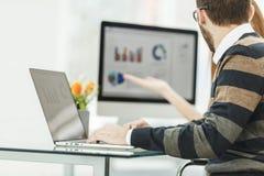 提供经费给研究有财政图和推销计划的膝上型计算机的专家 免版税库存照片