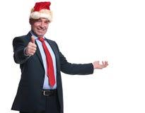提出和做好标志的圣诞老人帽子的商人 免版税库存照片