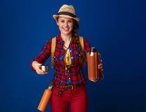 提出微笑的妇女的远足者从热水瓶的热的饮料 免版税图库摄影