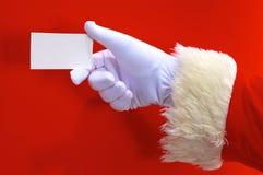 提出您的圣诞节文本或产品在红色背景的圣诞老人手与拷贝空间 库存图片
