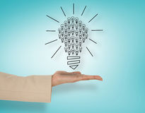 提出电灯泡的女性手的综合图象 免版税库存图片