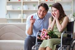 提出结婚提议的人对残疾妇女在轮椅 免版税库存照片