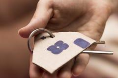 提出钥匙的女性手对房子,房地产开发商 免版税库存照片