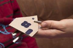 提出钥匙的女性手对房子,房地产开发商 库存图片