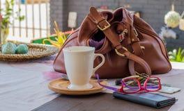 提包和好吃的东西在一张桌上在咖啡店 免版税库存照片