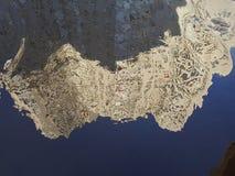 提取一座高层建筑物的被倒置的反射在一个水坑的与大海表面,下面是文本的空的空间在a 库存图片