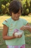 提取乳脂吃女孩冰木盆 免版税库存图片