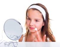 提取乳脂她的面孔的十几岁的女孩 库存图片