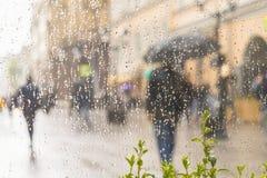 提取人被弄脏的剪影在伞,通过在玻璃窗的雨珠被看见的城市街道下,被弄脏 概念 免版税库存照片