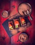 提拉米苏用草莓和巧克力粉末,组成在红色木背景 图库摄影