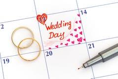 提示在日历的婚礼之日与圆环和笔 库存照片