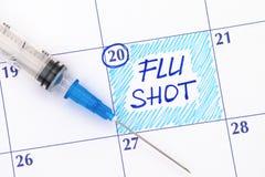 提示在日历的流感预防针与注射器 图库摄影