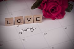 提示在日历计划的婚礼之日和在木头的情书 库存图片
