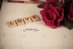 提示在日历计划的婚礼之日和在木头的情书 免版税库存照片