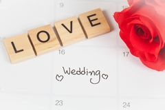 提示在日历计划的婚礼之日和在木头的情书 图库摄影
