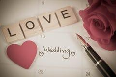提示在日历计划的婚礼之日和在木头的情书 库存照片
