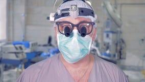 提起他的头和专心地凝视入照相机的专业医生 影视素材