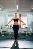 提高哑铃的妇女在健身房 库存图片