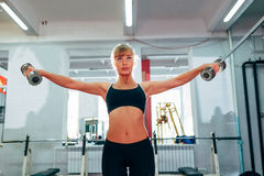 提高哑铃的妇女在健身房 免版税图库摄影