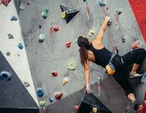 提高在攀岩墙壁的适合的运动的学生女孩在健身房 库存图片