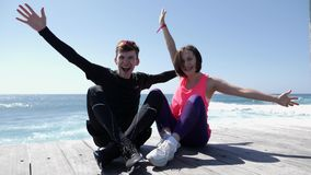 提高在海滩的年轻有吸引力的愉快的夫妇手悬而未决微笑的和欢呼的开会 t 股票视频