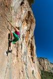 提高在高垂直的岩石的女性极端登山人的身体 免版税库存图片