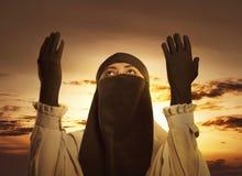 提高手和祈祷的hijab的年轻亚裔回教妇女 免版税库存照片