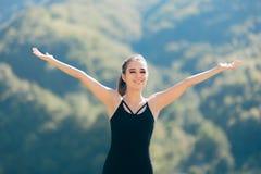 提高胳膊赞赏的美好的自然风景的激动的愉快的体育妇女 免版税库存图片