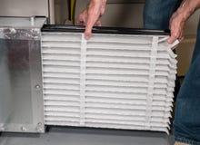 插入一个新的空气过滤器的老人在HVAC熔炉 免版税库存照片