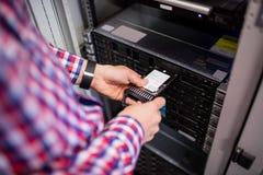 插入一个硬盘驱动器的技术员入刀片服务器 库存图片
