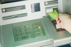 插入卡片的妇女手对ATM机器撤出金钱 图库摄影