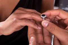 插入圆环的男性手入手指 免版税图库摄影