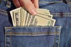 插入或撤出美国金钱美国货币,在蓝色牛仔裤的后面口袋的USD的堆男性手有黄色stitchin的 库存照片