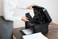 插入激光弹药筒的女实业家在打印机 免版税库存照片