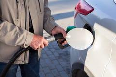 插入燃料喷嘴的资深男性手在汽油刺激的一辆汽车 库存图片