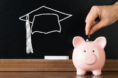 插入硬币的人在完成的教育Piggybank 免版税库存图片
