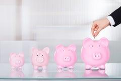 插入硬币的商人在piggybank在办公桌 免版税库存图片