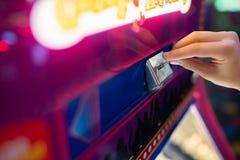 插入硬币的孩子入机器在游乐园 免版税库存图片