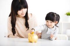 插入硬币的母亲和女儿在存钱罐中 图库摄影