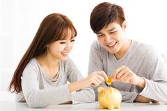 插入硬币的年轻夫妇在Piggybank 库存照片
