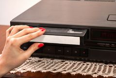 插入空白的VHS卡式磁带的妇女手在老录影机 库存照片