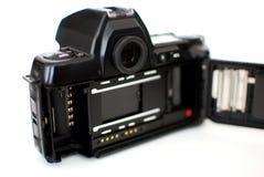 从插入35 mm影片的后面生动描述的模式SLR照相机 免版税库存图片