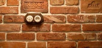插口和开关在砖墙上 免版税图库摄影
