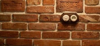 插口和开关在砖墙上 库存照片