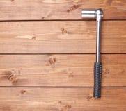 插口有黑把柄的金属板钳木表面上 免版税库存图片