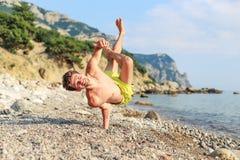握一个手指在异常的位置的海滩的愉快的人 免版税库存图片